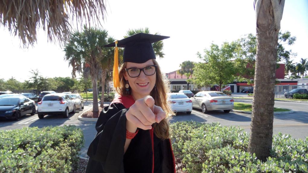 Uśmiechnięta studentka spogląda na wprost i wskazuje palcem wskazującym na wprost.
